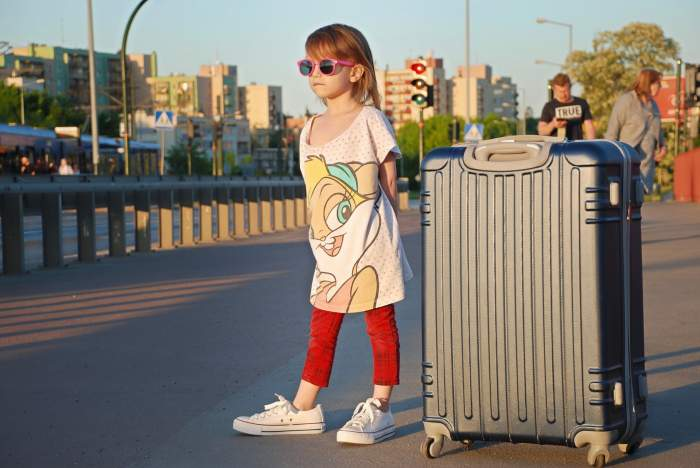 Young girl traveling with a large suitcase
