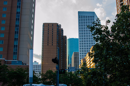 A few buildings in the Houston skyline partially obscured by trees