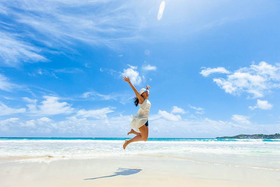 Woman in white coverup and hat jumping on the beach in Punta Cana, Dominican Republic